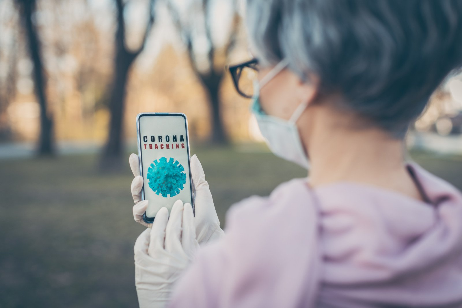 Woman using coronavirus tracking app on her phone